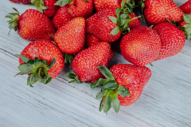 Vista lateral de fresas frescas maduras en madera blanca