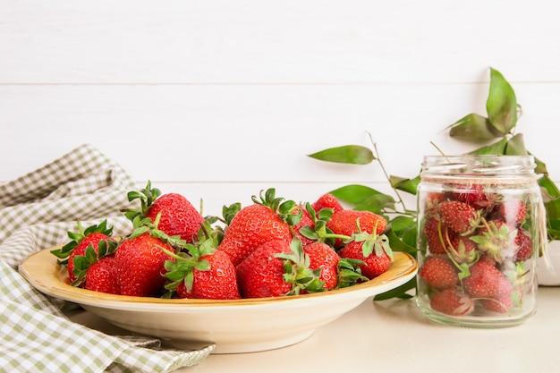 Vista lateral de fresas maduras frescas en placa en blanco