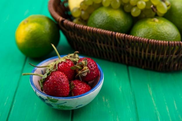 Vista lateral de fresas en un platillo con mandarinas y uvas en una canasta sobre una pared verde