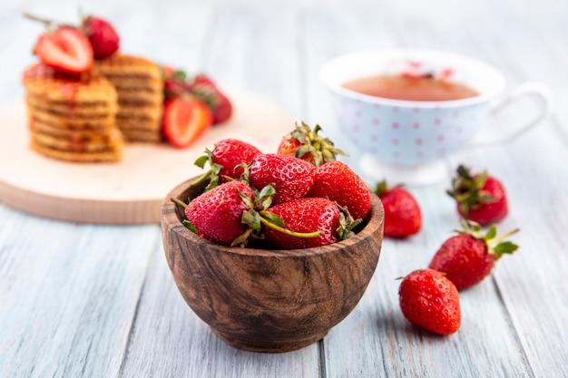 Vista lateral de fresas en un tazón con té y galletas waffle sobre madera