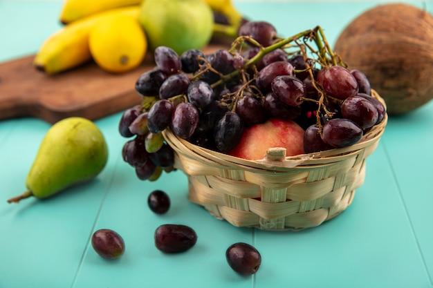 Vista lateral de frutas como canasta de uva y melocotón con plátano manzana limón sobre tabla de cortar y coco pera sobre fondo azul.