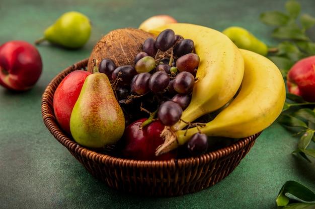 Vista lateral de frutas como coco, plátano, uva, pera, melocotón en canasta con hojas sobre fondo verde