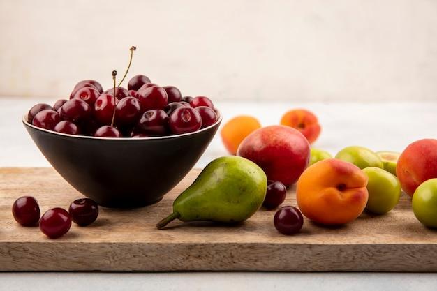 Vista lateral de frutas como melocotón pera ciruela albaricoque con tazón de cereza sobre tabla de cortar sobre fondo blanco.