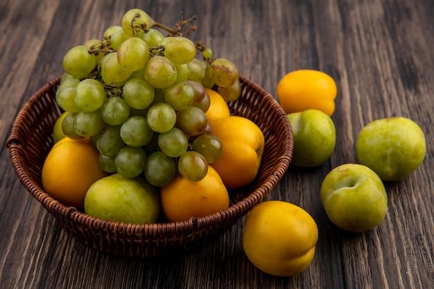 Vista lateral de frutas como pluot verde uva y nectacots en canasta y patrón de pluots y nectacots sobre fondo de madera