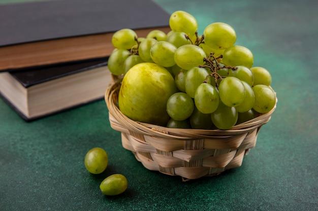 Vista lateral de frutas como uva y pluot en canasta con libros cerrados sobre fondo verde