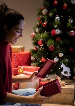 Vista lateral fsmiley mujer abriendo regalo