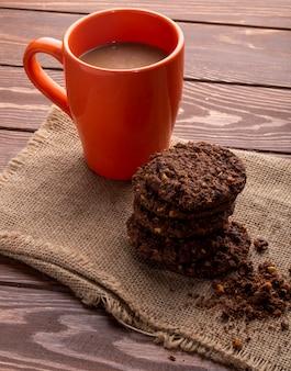 Vista lateral de galletas de avena con chispas de chocolate y cacao y una taza con bebida de cacao en madera
