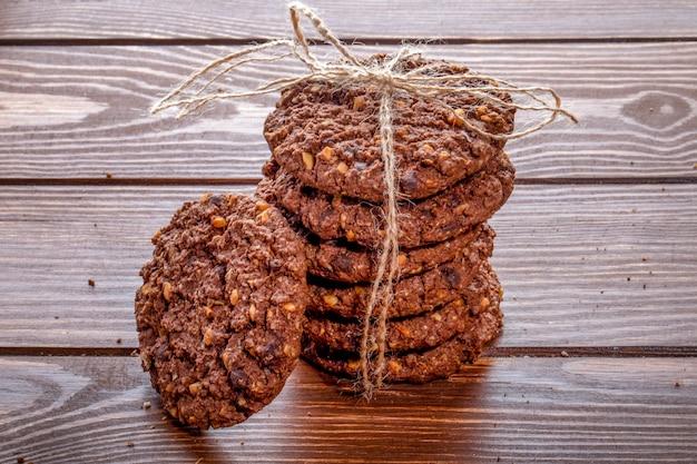 Vista lateral de las galletas de chispas de chocolate con cereales, nueces y cacao atados con una cuerda sobre fondo de madera