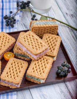 Vista lateral de galletas con mermelada de bayas rellenas en una bandeja de madera