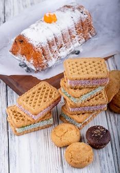 Vista lateral de galletas con mermelada de bayas rellenas en rústico
