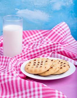 Vista lateral de galletas en un plato blanco servido con un vaso de leche en rosa