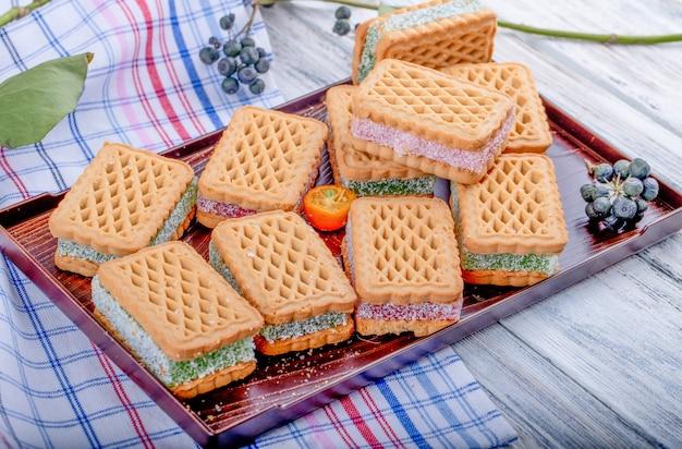 Vista lateral de galletas con relleno de bayas de mermelada en una bandeja de madera