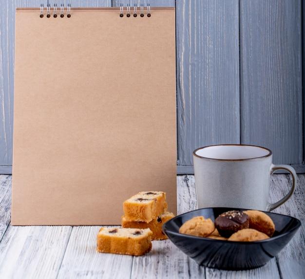 Vista lateral de galletas en un tazón y una taza de té en rústico