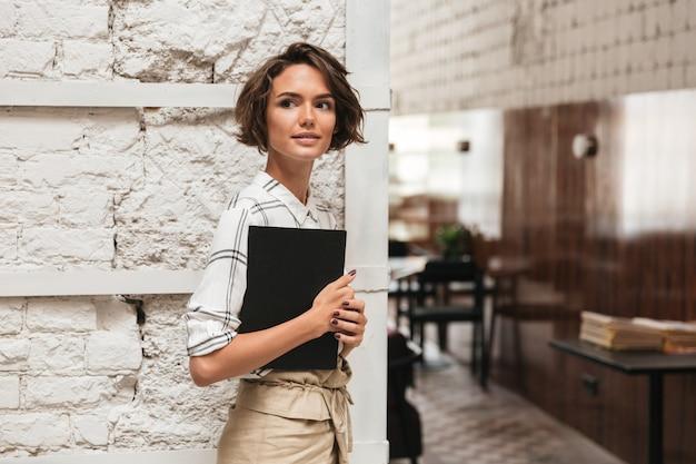 Vista lateral del gerente femenino rizado que sostiene la carpeta en la mano