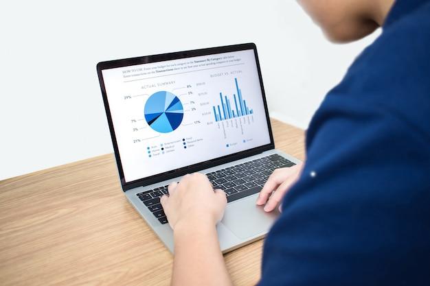 Vista lateral de gráficos humanos que mecanografían en los ordenadores portátiles en los escritorios de trabajo modernos en la oficina.