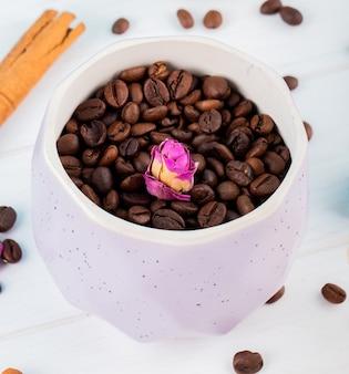 Vista lateral de los granos de café en un recipiente sobre fondo blanco.
