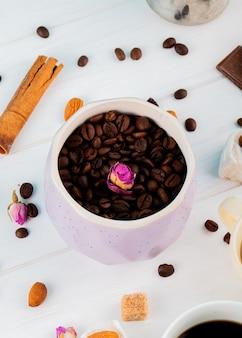 Vista lateral de los granos de café en un tazón y palitos de canela sobre fondo blanco.