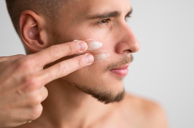 Vista lateral del guapo aplicando crema en el rostro