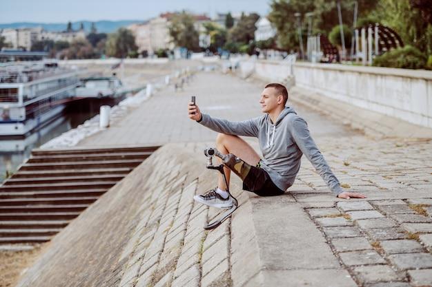 Vista lateral del guapo deportista discapacitado caucásico en ropa deportiva y pierna artificial sentado en el muelle y tomando selfie.