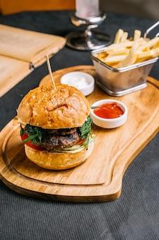 Vista lateral hamburguesa de carne con empanada de carne de res verduras de tomate lechuga en bollos de hamburguesa con papas fritas mayonesa y salsa de tomate en un plato