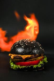 Vista lateral de hamburguesa de carne negra con lechuga, tomate, pepino y queso