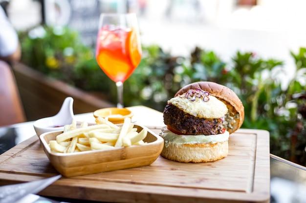 Vista lateral hamburguesa con empanada de ternera cebolla roja a la parrilla tomate lechuga en bollos de hamburguesa papas fritas y bebida de naranja sobre la mesa