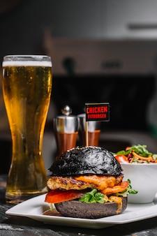 Vista lateral de una hamburguesa negra con chuleta de pollo, queso derretido y verduras en un plato con un vaso de cerveza sobre la mesa