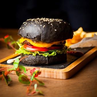 Vista lateral hamburguesa negra con papas fritas y salsa de tomate y flores en bandeja de madera sobre mesa de madera