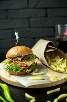 Vista lateral hamburguesa con papas fritas y pimiento verde en pizarra
