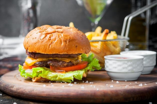 Vista lateral hamburguesa con papas fritas y tazón de salsa y una cesta de freír en bandeja de comida de madera en el restaurante