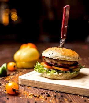 Vista lateral hamburguesa de pollo con hojas de lechuga empanada de pollo con tomate en bollos de hamburguesa y pimienta negra sobre la mesa