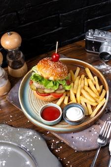 Vista lateral de hamburguesa de pollo con pepinillos y tomates servidos con papas fritas y salsas en la oscuridad