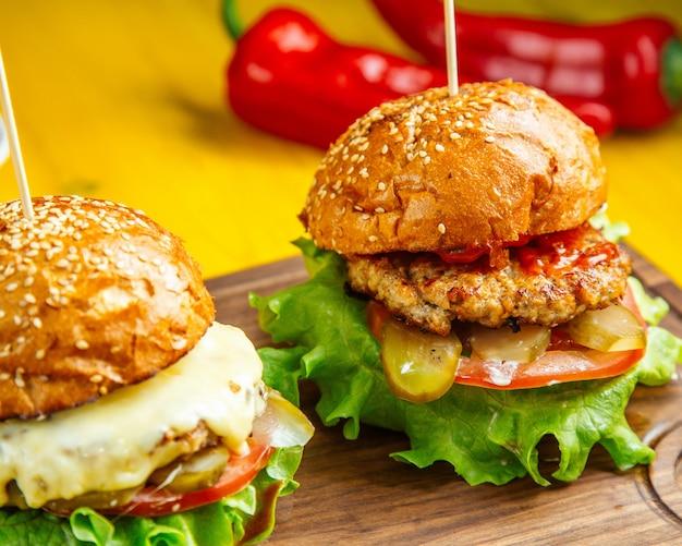 Vista lateral de hamburguesas con chuleta de pollo queso derretido tomates y encurtidos sobre tabla de madera