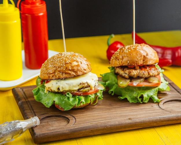 Vista lateral de hamburguesas con chuleta de pollo, queso fundido y tomates sobre tabla de madera