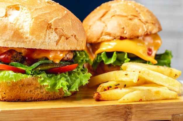 Vista lateral hamburguesas hamburguesa de pollo con queso tomate pepino encurtido y lechuga entre bollos de pan