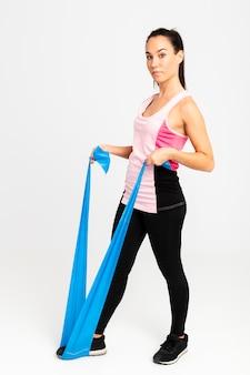 Vista lateral hembra joven en estiramiento de gimnasio