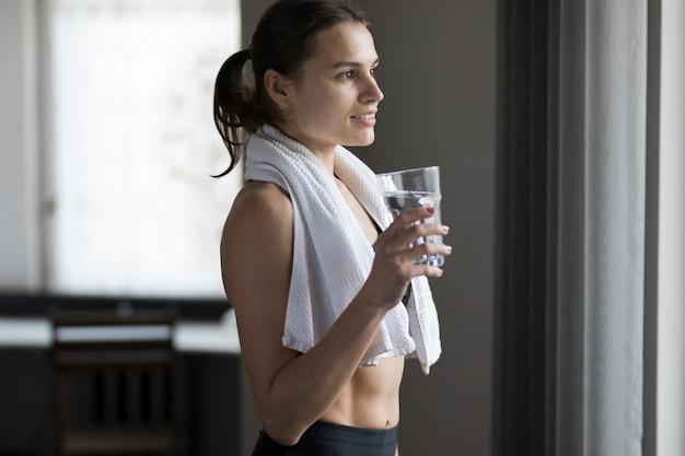 Vista lateral de la hembra con un vaso de agua y una toalla sobre los hombros