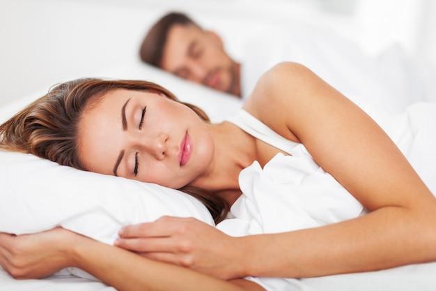 Vista lateral de la hermosa joven pareja durmiendo en la cama en casa