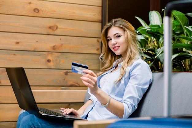Vista lateral de la hermosa joven que trabaja en la computadora portátil y muestra la tarjeta de crédito