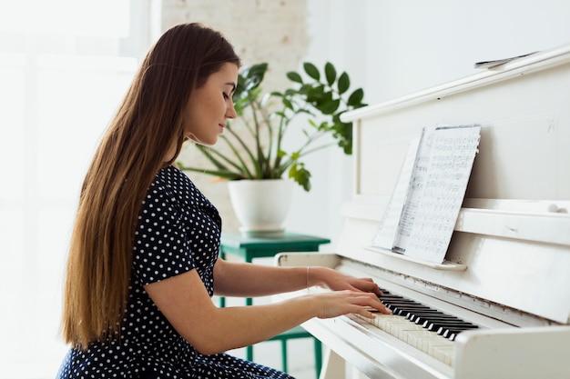 Vista lateral de una hermosa joven tocando el piano