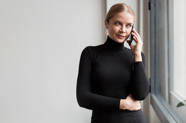 Vista lateral hermosa mujer hablando por teléfono