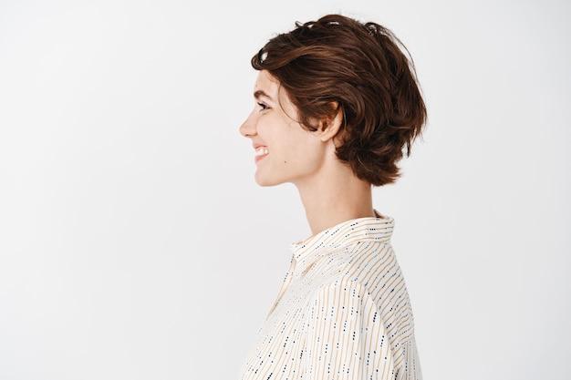 Vista lateral de la hermosa mujer joven con piel limpia y saludable, aspecto natural sin maquillaje, mirando a la izquierda y sonriendo, de pie sobre una pared blanca
