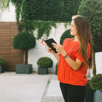 Vista lateral de una hermosa mujer leyendo el diario