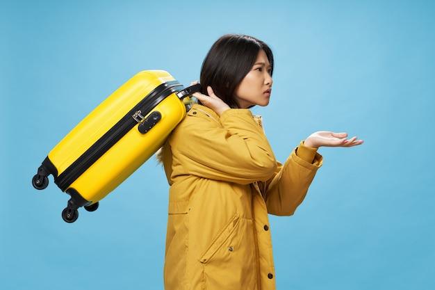 Vista lateral de una hermosa mujer con una maleta embarcándose en un viaje
