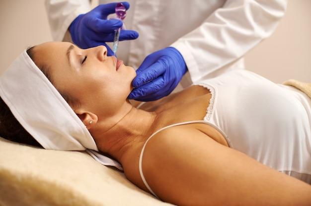 Vista lateral de una hermosa mujer recibiendo tratamiento de estiramiento facial en el salón de spa