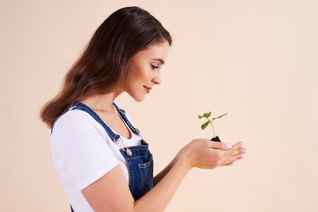 Vista lateral de la hermosa mujer sosteniendo pequeñas plántulas