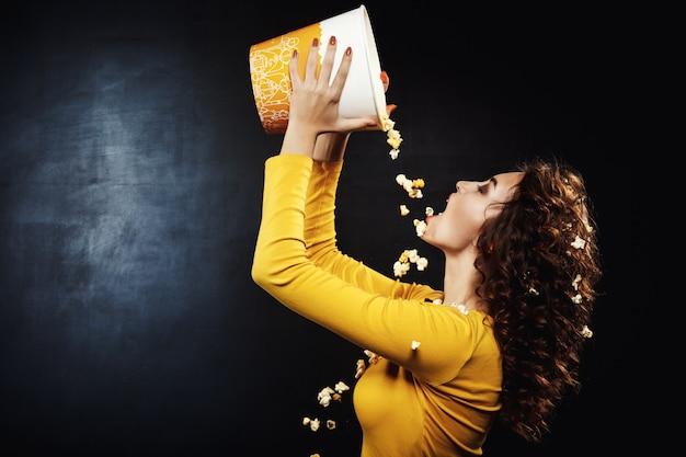 Vista lateral de hermosa mujer vertiendo cursi palomitas de maíz del cubo