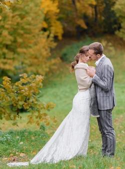 Vista lateral de hermosos recién casados de pie en el parque y el novio abraza a su amada
