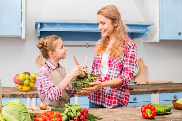 Vista lateral de una hija ayudando a su madre para preparar ensalada