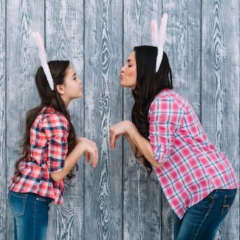 Vista lateral de la hija y la madre posando como un conejito haciendo pucheros contra el fondo de madera gris